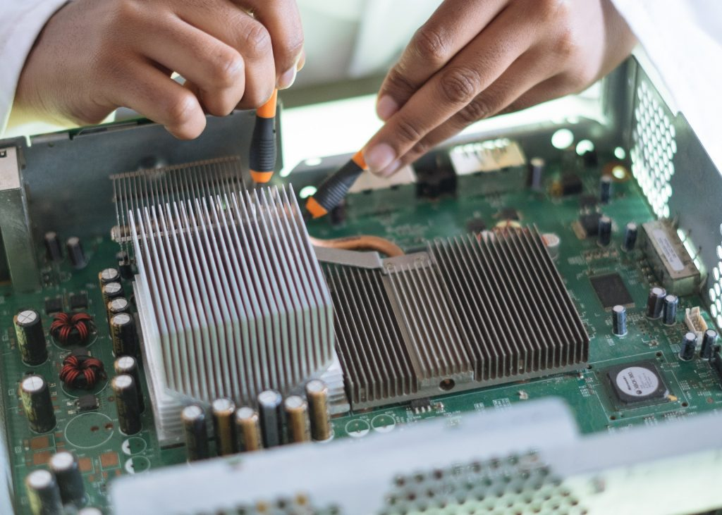 crop-technician-checking-contacts-on-motherboard-in-workshop-3825581